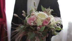 Stilig brudguminnehavgrupp av att gifta sig blommor för fokusförgrund för 3 bukett bröllop långsam rörelse arkivfilmer
