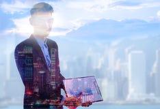 Stilig businessperson som anv?nder b?rbara datorn p? abstrakt stads- och himmelbakgrund med kopieringsutrymme svart telefon f?r k arkivbilder