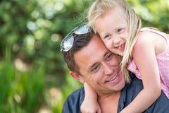 Stilig Caucasian fader och dotter som har gyckel på parkera Royaltyfria Bilder