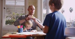Stilig caucasian fader som klottrar med hans två pojkar Arkivfoto