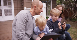 Stilig caucasian fader som ser den handheld apparaten med barn Royaltyfria Foton
