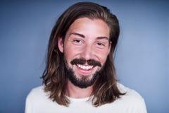 Stilig caucasian man med långt brunt hår mot blå bakgrund Royaltyfria Foton