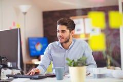 Stilig Caucasian man på arbetsskrivbordet som vänder mot datoren för plan skärm arkivfoton