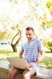 Stilig caucasian man som använder att sitta för bärbar dator som är utomhus- i en parkera Sommarsolskendag Begrepp av ungt affärs royaltyfria foton