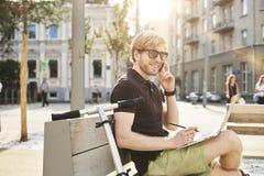 Stilig caucasian man som använder att sitta för bärbar dator som är utomhus- i en parkera Sommarsolskendag Begrepp av ungt arbeta fotografering för bildbyråer