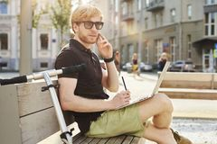 Stilig caucasian man som använder att sitta för bärbar dator som är utomhus- i en parkera Sommarsolskendag Begrepp av ungt arbeta royaltyfria bilder
