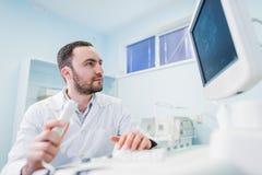 Stilig doktor som använder en ultraljudmaskin royaltyfria bilder