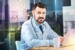 Stilig doktor som ler, medan sitta framme av hans bärbar dator arkivfoton