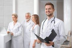 Stilig doktor som poserar, grupp av terapeuter som bakom står royaltyfria foton