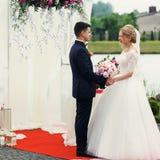 Stilig elegant brudgum och härlig blond brud som tar löften på Fotografering för Bildbyråer
