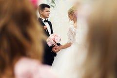 Stilig elegant brudgum och härlig blond brud som tar löften på Royaltyfri Foto
