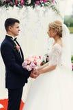 Stilig elegant brudgum och härlig blond brud som tar löften på Arkivbilder