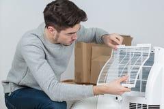 Stilig elektriker för ung man som installerar luft som betingar i klienthus arkivfoton