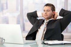 Stilig executive sitting på skrivbordsträckning royaltyfria bilder