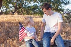 Stilig fader och hans hållande amerikanska flaggancelebra för liten son royaltyfri fotografi