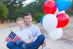 Stilig fader som rymmer färgrika ballonger och hans lilla sonhol Arkivfoton