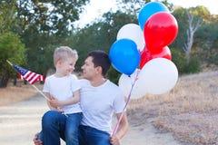 Stilig fader som rymmer färgrika ballonger och hans lilla sonhol Arkivbilder