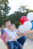 Stilig fader som rymmer färgrika ballonger och hans lilla sonhol Royaltyfri Foto