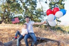 Stilig fader som rymmer färgrika ballonger och hans lilla sonhol Royaltyfria Foton