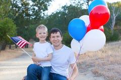Stilig fader som rymmer färgrika ballonger och hans lilla sonhol Arkivfoto