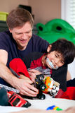 Stilig fader som spelar bilar med den rörelsehindrade sonen Arkivfoton