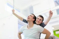 stilig flickvän hans man som piggybacking royaltyfri foto