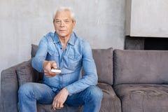 Stilig flott gentleman som kopplar av på en soffa royaltyfria foton