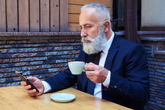 Stilig gamal man som dricker kaffe, medan surfa i mobiltelefon Royaltyfri Fotografi