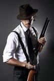 Stilig gangster som poserar med hagelgeväret och hatten fotografering för bildbyråer
