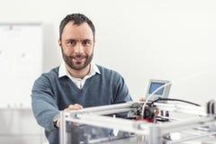 Stilig gladlynt man som poserar nära skrivaren 3D Royaltyfri Bild