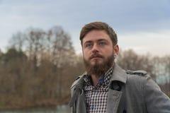 stilig grabb en man står på bankerna av floden höstmannen royaltyfria foton