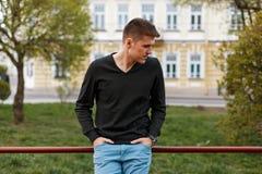 Stilig grabb i en svart skjorta som från sidan ser fotografering för bildbyråer