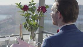 Stilig grabb i ett stilfullt omslag som sitter med hans baksida till kameran på en tabell i ett kafé eller en restaurang Manvändn stock video