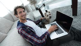 Stilig grabb med bärbara datorn som kramar hans hund och sitter nära soffan arkivbild