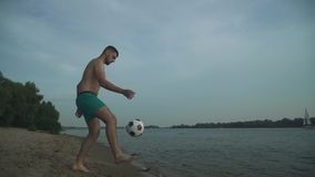 Stilig grabb med en fotboll på flodbanken lager videofilmer
