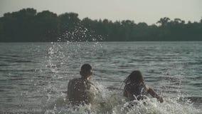 Stilig grabb och härliga flickahållhänder och körning in i floden lager videofilmer