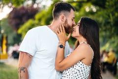 Stilig grabb och härliga flickor som kysser i parkera arkivfoton