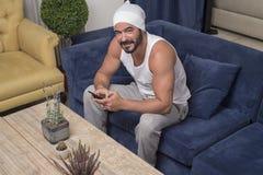 Stilig grabb som använder smartphonen, stiligt mansammanträde på soffan på royaltyfri bild