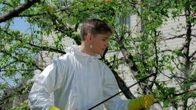 Stilig grabb som besprutar kemikalieer i trädgården arkivfilmer