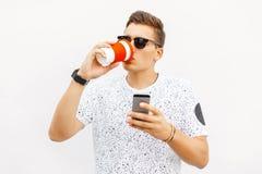 Stilig grabb som dricker kaffe och läsning ett meddelande på din telefon arkivbilder