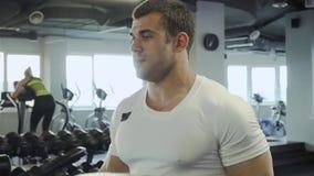 Stilig grabb som gör övningar med hantlar i idrottshallen lager videofilmer