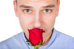 Stilig grabb som luktar den röda rosen Arkivfoton