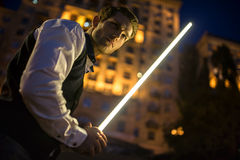 Stilig grabb som rymmer en lightsaber Jedi arkivfoton