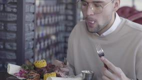 Stilig grabb som sitter i lyxig restaurang och eatting enorm läcker maträtt med grillade kött och grönsaker arkivfilmer