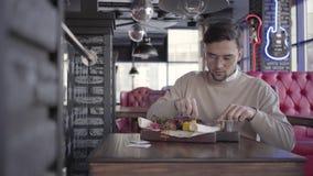 Stilig grabb som sitter i lyxig restaurang och eatting enorm läcker maträtt med grillade kött och grönsaker lager videofilmer