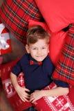 Stilig gullig pojke som nästan firar för nytt år för jul trädet för xmas bara på den röda kudden som poserar i bärande jeans för  Arkivbilder