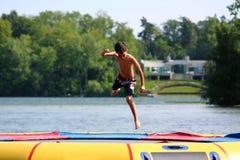 Stilig gullig pojkebanhoppning på en vattentrampolin som svävar i en sjö i Michigan under sommar royaltyfri bild