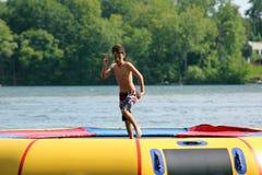 Stilig gullig pojkebanhoppning på en vattentrampolin som svävar i en sjö i Michigan under sommar arkivfoton