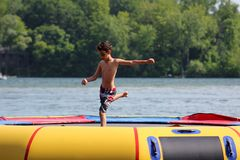 Stilig gullig pojkebanhoppning på en vattentrampolin som svävar i en sjö i Michigan under sommar royaltyfri foto