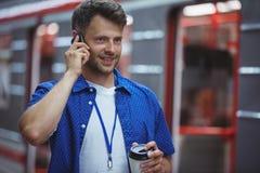 Stilig hållande disponibel kopp, medan tala på mobiltelefonen Arkivfoton